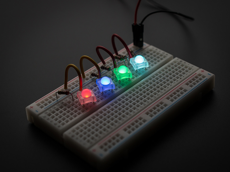 Four square LEDs wired to breadboard and different colors