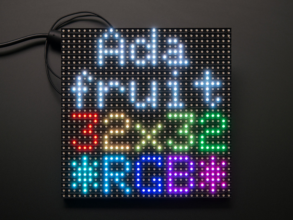 "Assembled and powered on 32x32 RGB LED Matrix Panel - 6mm pitch. The matrix lights up ""Adafruit 32x32 *RGB*"""