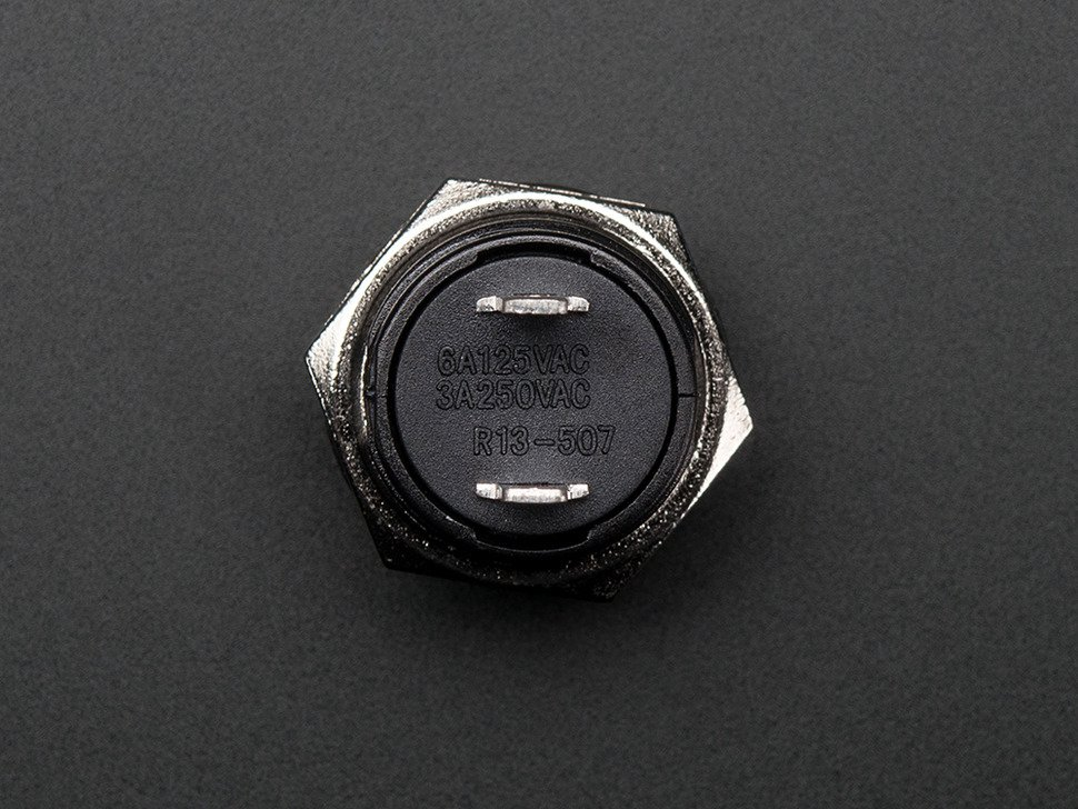 Reverse shot of panel mount pushbutton showing two leads.