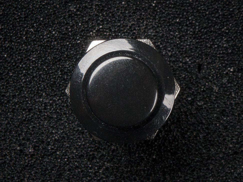 Top-down shot of 16mm black panel mount pushbutton.