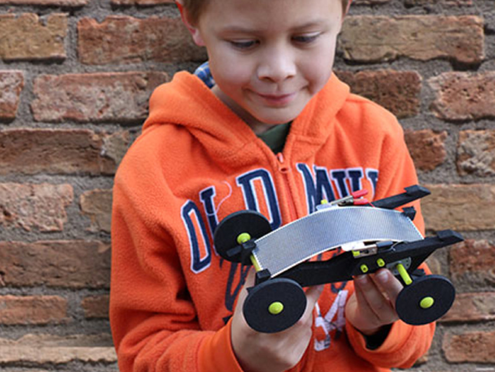 young child looking at assembled racer toy