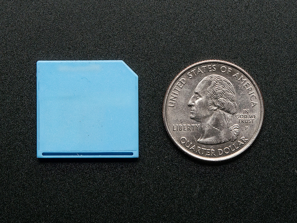 Shortening MicroSD card adapter next to quarter for size reference, front of card