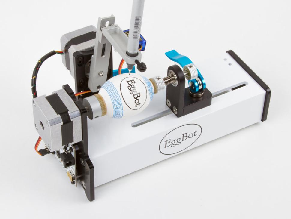 A slick robot drawing an intricate design onto an egg with a sharpie pen.