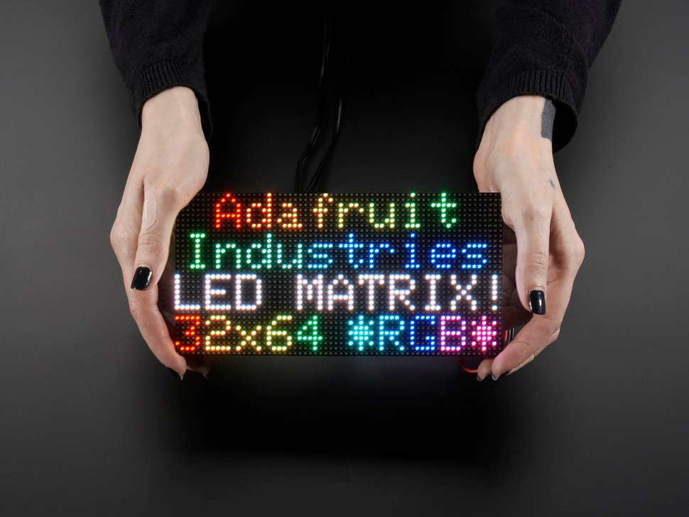 """Two white hands hold out an assembled and powered on 64x32 RGB LED Matrix Panel - 3mm pitch. The matrix displays """"Adafruit Industries LED MATRIX! 32x64 *RGB*"""""""