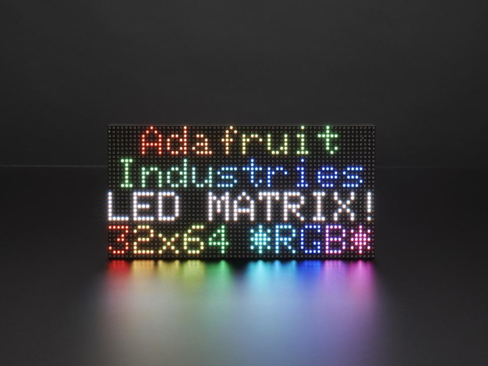 "Assembled and powered on 64x32 RGB LED Matrix Panel - 3mm pitch. The matrix displays ""Adafruit Industries LED MATRIX! 32x64 *RGB*"""