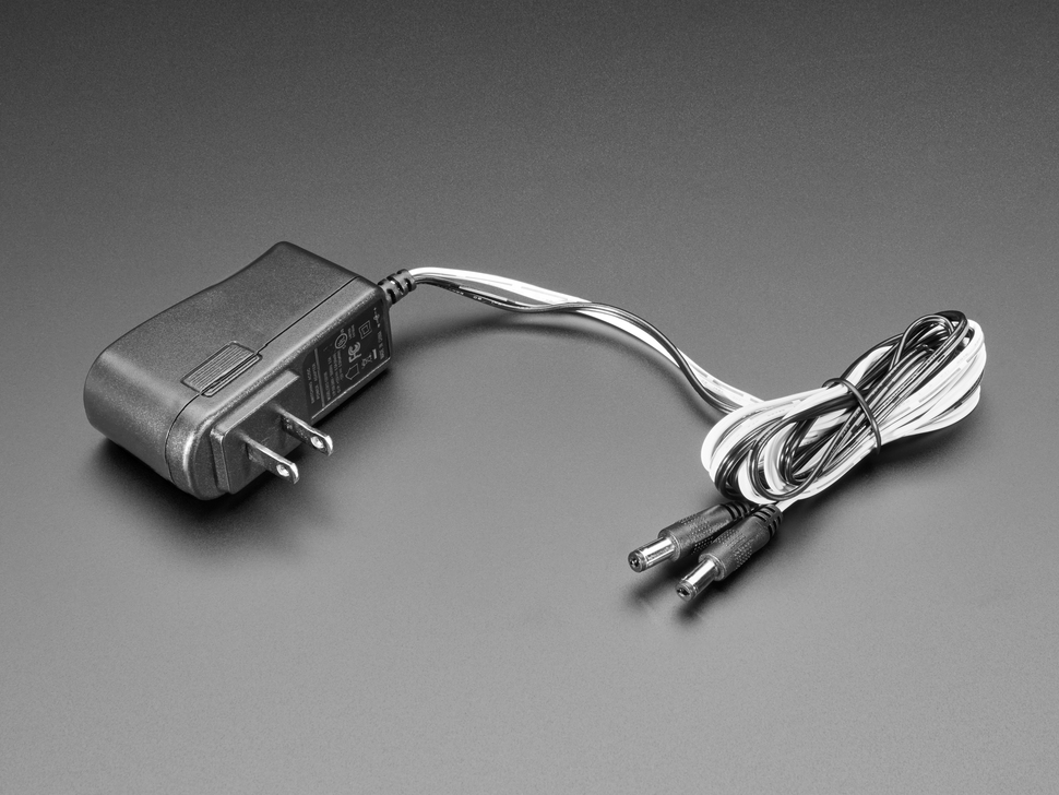 Wall wart power supply with two 2.1mm DC outputs.