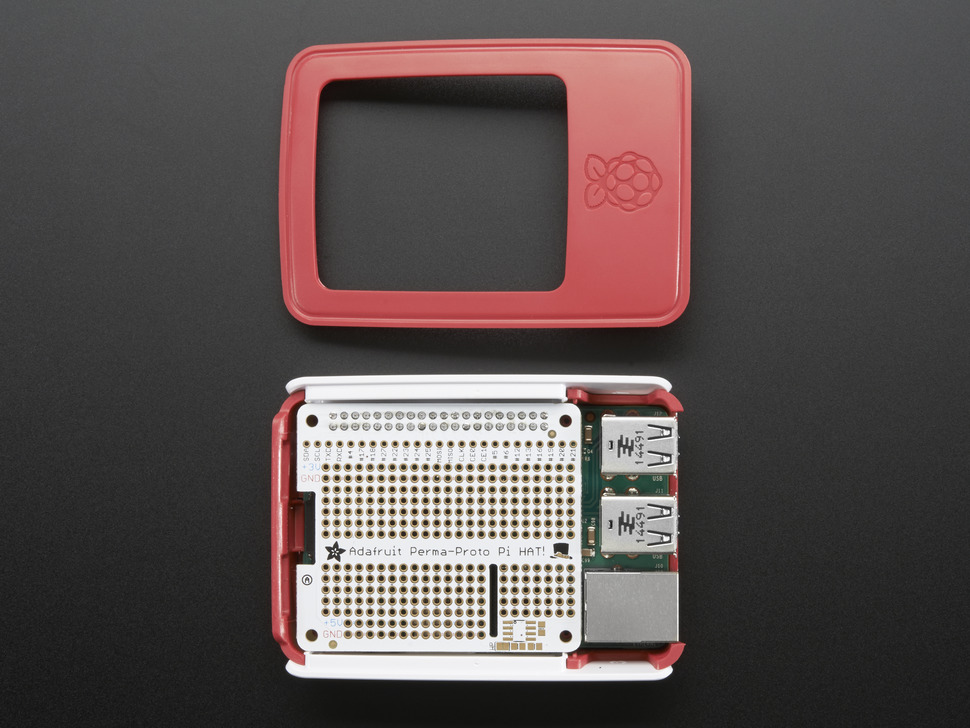 Half-assembled red and white Raspberry Pi case with the lid off and a perma-photo HAT installed.