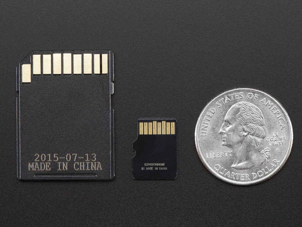 Back of SD adapter, micro SD card, next to quarter