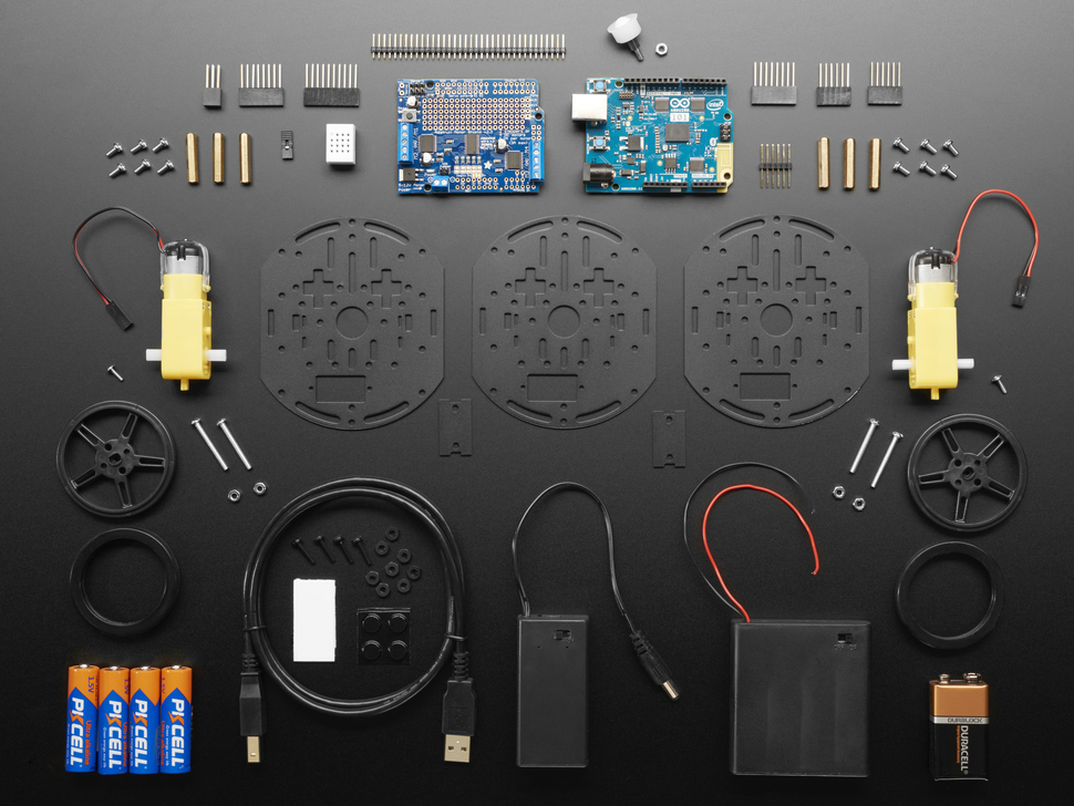 Kit component shot with round metal pieces, Arduino, shield, wheels, motors and other hardware.