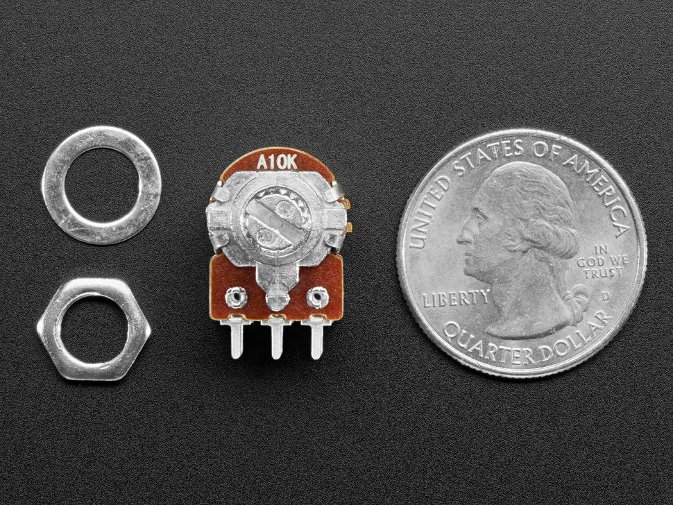 Potentiometer and mounting hardware detail next to US quarter.