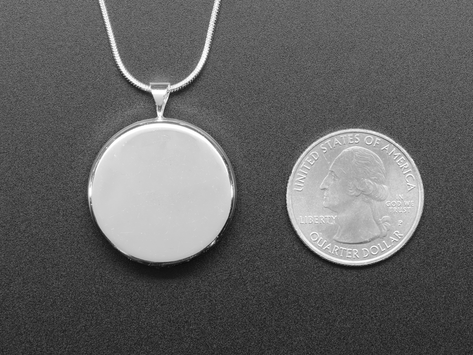 Back of the pendant show with a quarter for scale