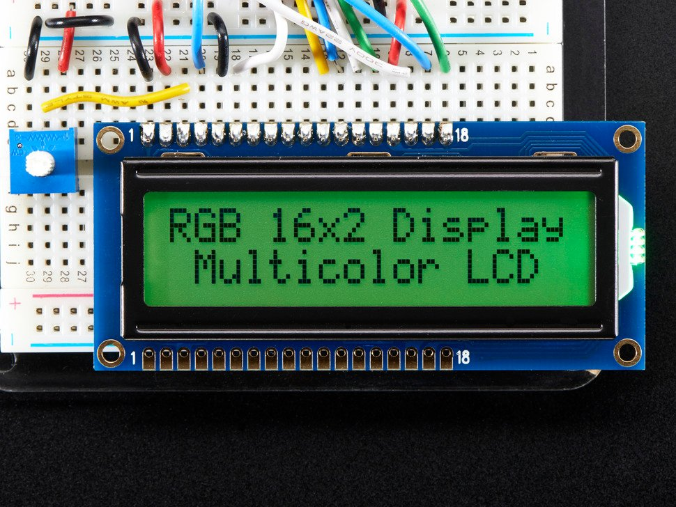 """LCD wired on breadboard with text displayed: """"RGB 16x Display Mulitcolor LCD"""" with green backlight"""