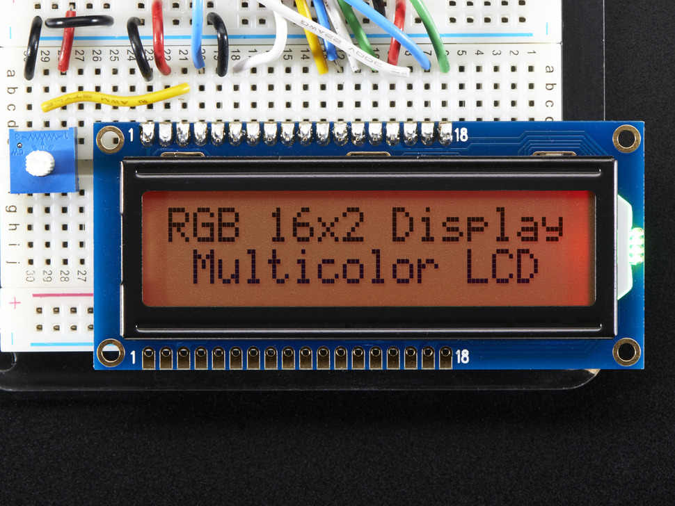 """LCD wired on breadboard with text displayed: """"RGB 16x Display Mulitcolor LCD"""" with red backlight"""