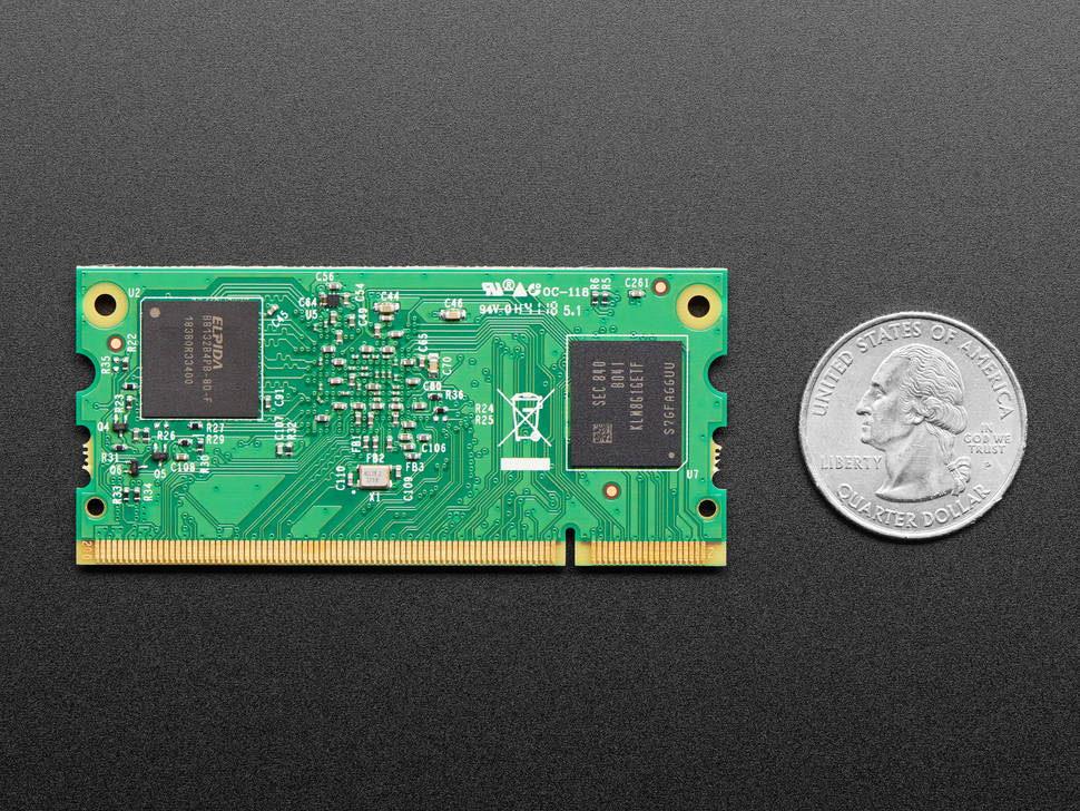 Top of Raspberry Pi Compute Module showing RAM and FLASH chip, next to Quarter