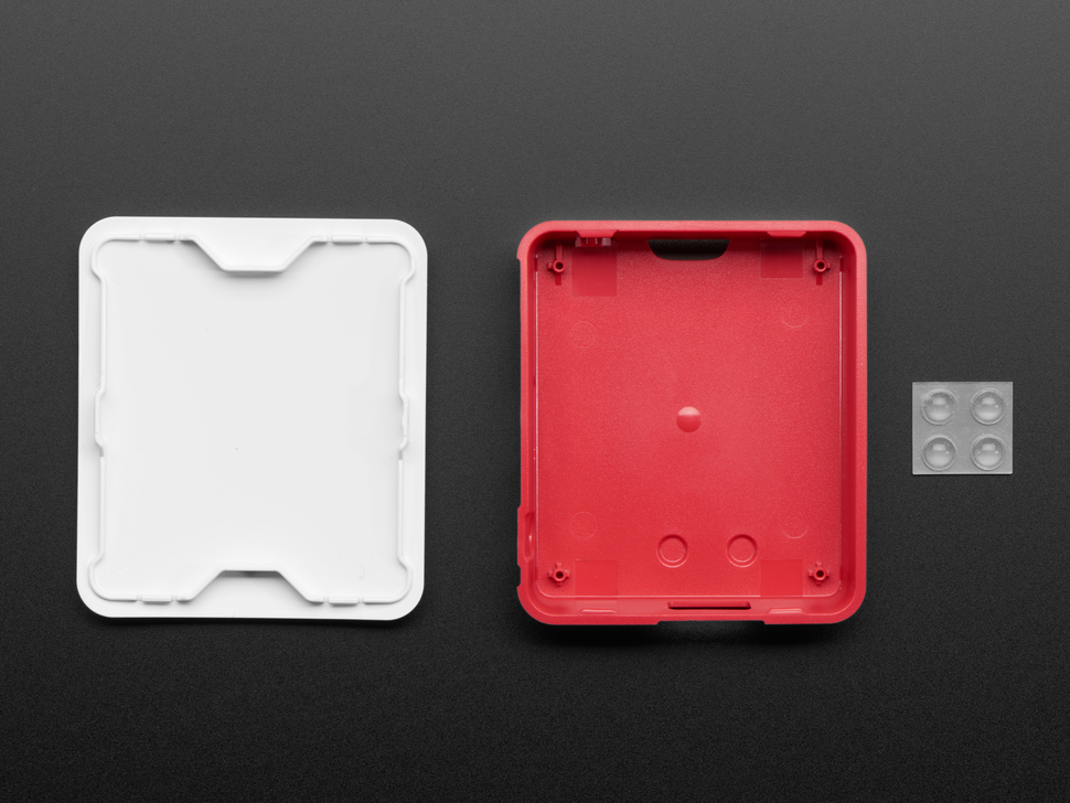 Lid and base pieces of Raspberry Pi Model 3 A+ case next to clear rubber feet.