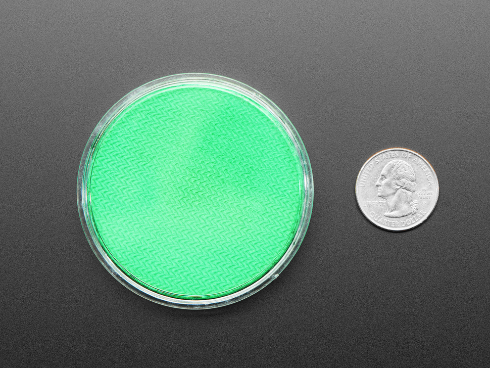Round green disc of fluorescent paint next to US quarter.