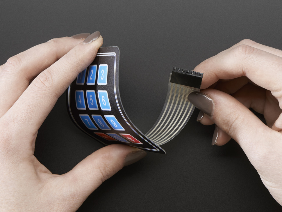 Two hands bending keypad to show flexibility