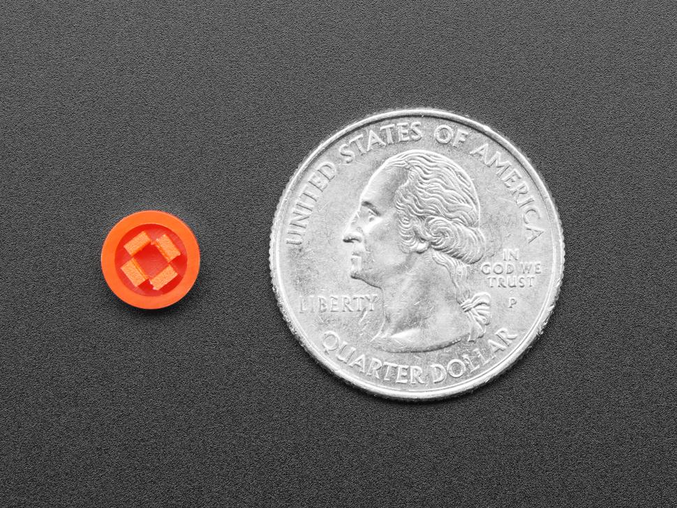 Single orange 8mm plastic button cap next to US quarter