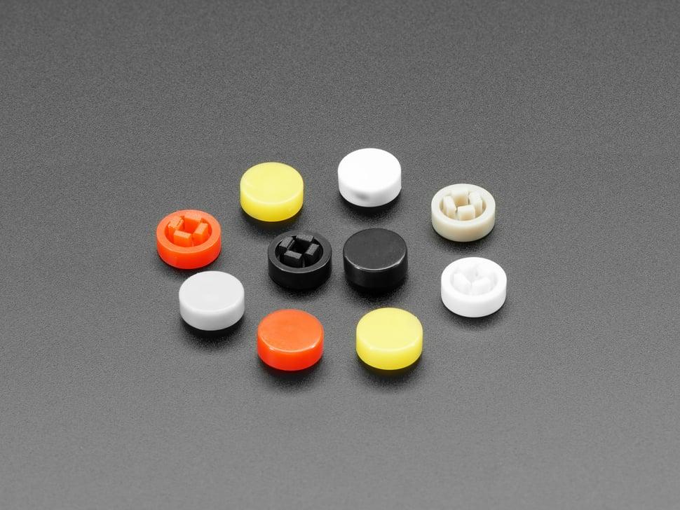 Angled shot of 10 plastic button caps colored reddish-orange, yellow, white, and black.