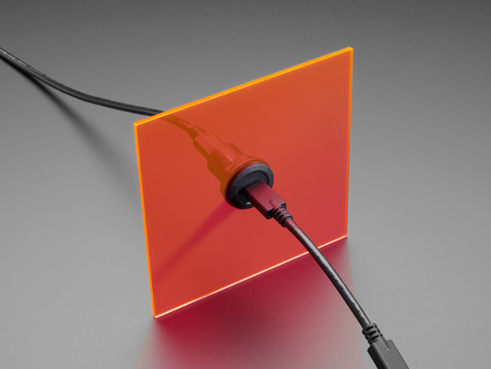 Panel mount adapter set in flat orange square. Cables connected to both ends of adapter