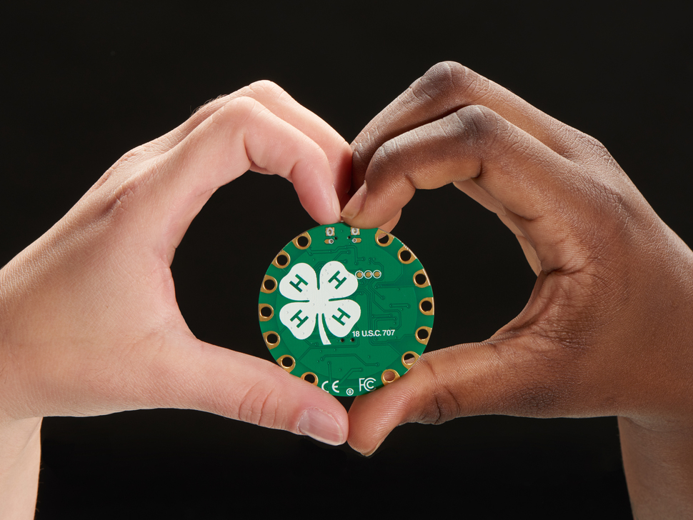 A white hand and a Black hand meet at the center of the frame to create a heart symbol. They hold up a round green dev board with the 4-H logo in white.