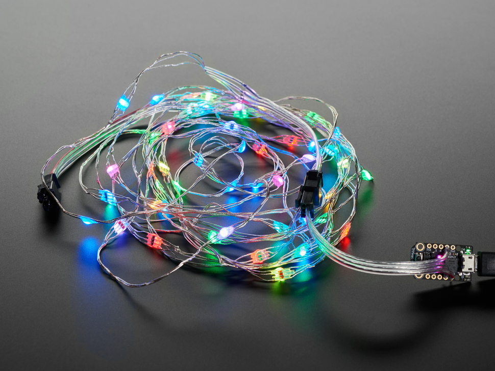 Adafruit Soft Flexible Wire NeoPixel Strand, coiled up wired to microcontroller and lit in rainbows