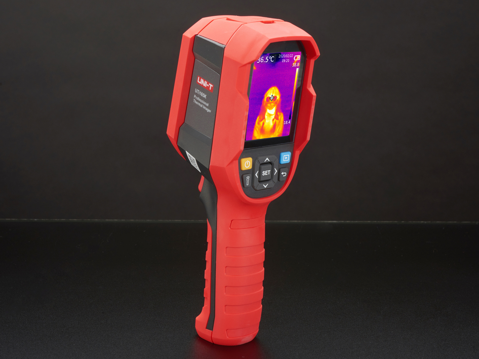 Thermal camera displaying a thermal image on it's lcd screen. Camera is red and grey, with the screen at the top of the camera and a handle at the bottom