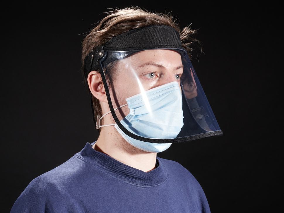 Face shield shown being worn by a model with a face mask. Face shield has a black headband
