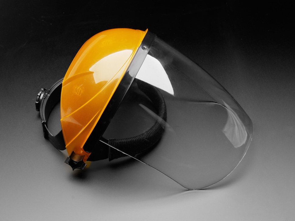 Face shield shown laying flat. The top of the shield that goes over the head is orange