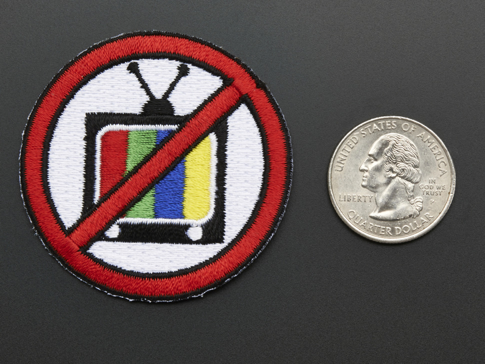 Circular badge with an image of a television crossed out with red line, next to a quarter for scale