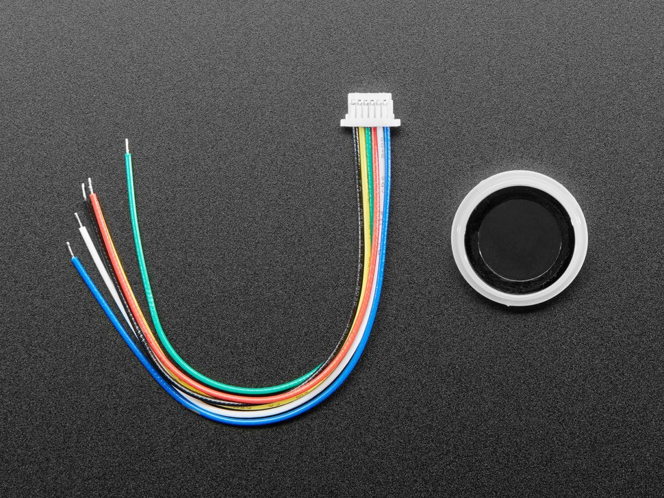 Top-down shot of round fingerprint sensor with 6-pin cable.