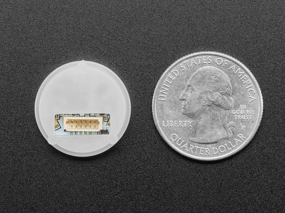 Round fingerprint sensor next to US quarter.
