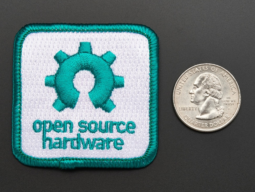 Square embroidered badge with partial gear logo and the words Open Source Hardware in turquoise, on white background with turquoise edging.