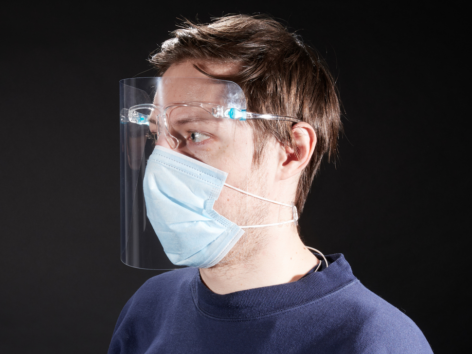 Face shield with glasses frame shown on a model wearing a blue face mask