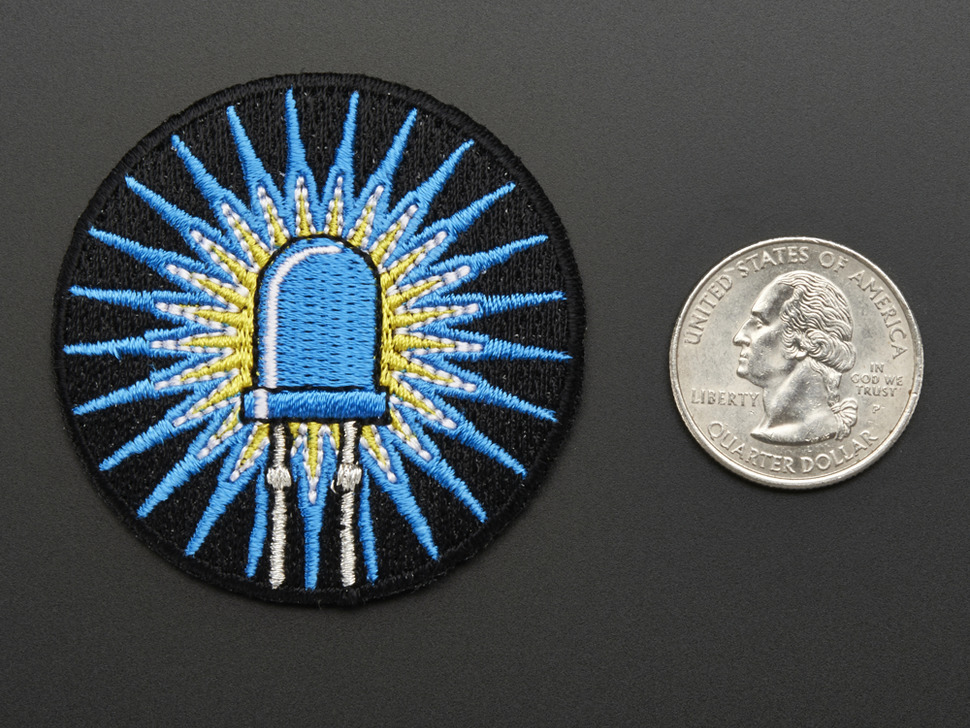 Circular embroidered badge of blue LED with rays of light on black background