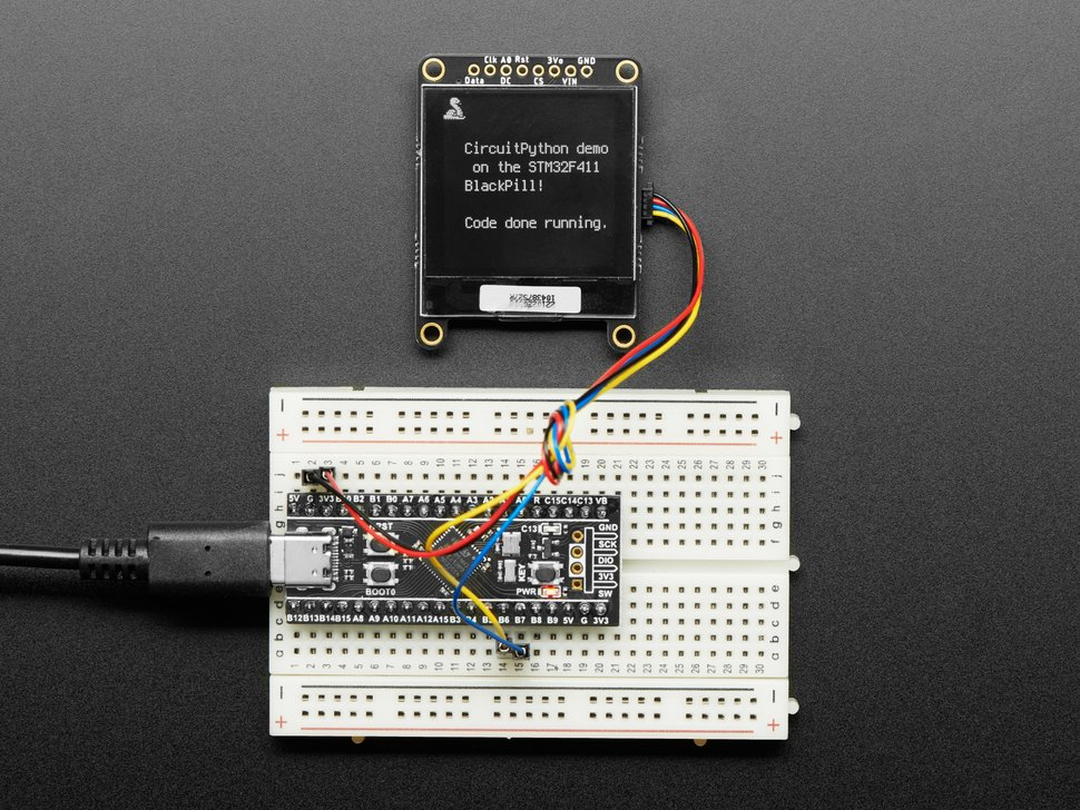 """Top-down shot of assembled STM32F411 dev board plugged into a breadboard with jumper wires. It is connected to a monochrome OLED display. It reads: """"CircuitPython demo on the STM32F411 BlackPill! Code done running."""""""