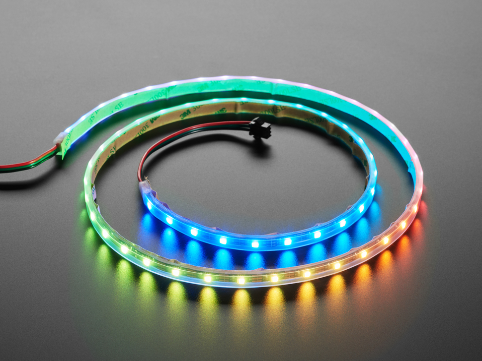 Angled shot of loosely coiled LED strip emitting green, blue, and yellow-orange lights.