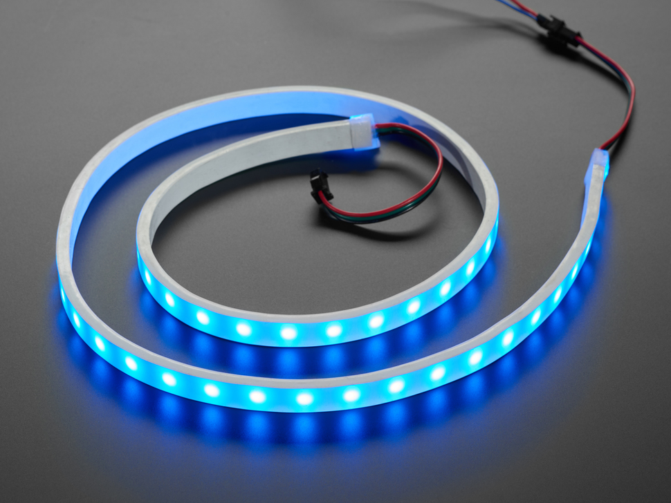 Angled shot of loosely coiled LED strip flashing blue LEDs.