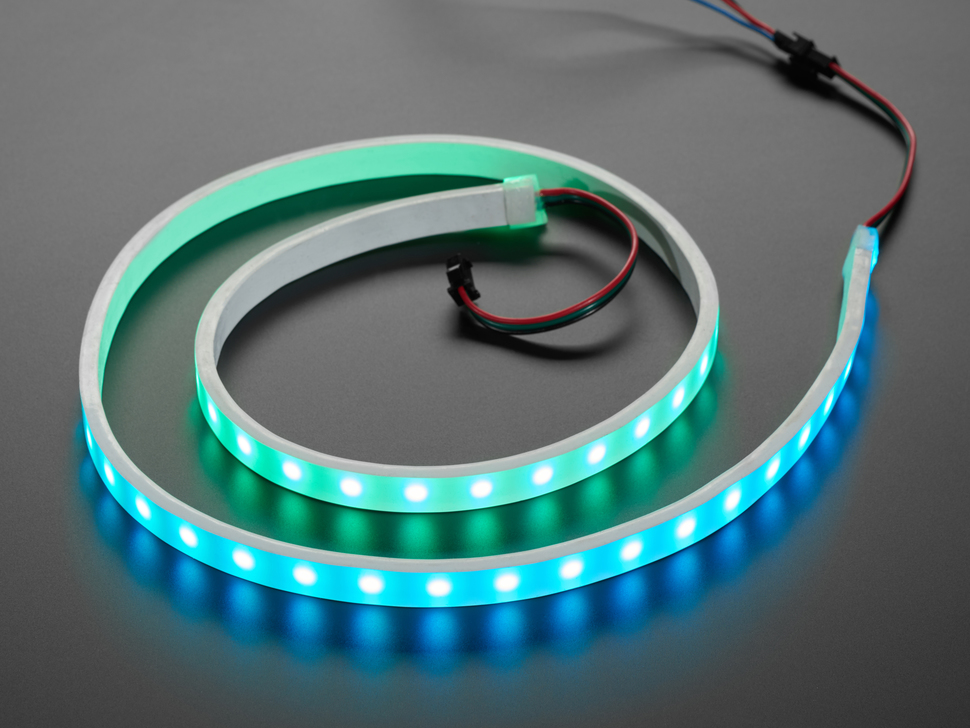 Angled shot of loosely coiled LED strip flashing blue and green LEDs.