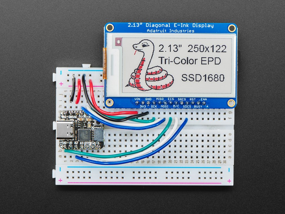 """Top view of a 2.13"""" tri-color eInk display assembled on a breadboard with jumper wires and a QT Py. Friendly snake in white-and-red, Blinka, on the display."""