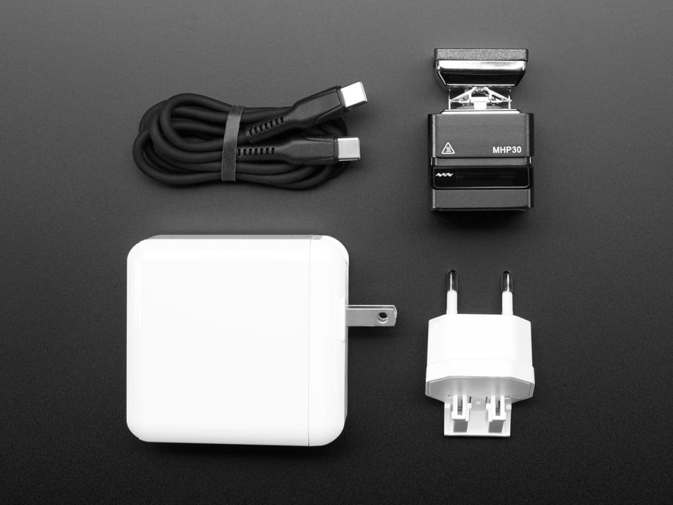 Top-down shot of mini burner, power supply block, EU plug adapter, and USB-C cable.