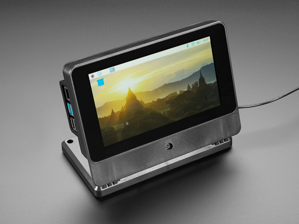 Angled shot of assembled SmartPi Touch Pro. The touchscreen displays a wallpaper of a European cityscape at sunrise.