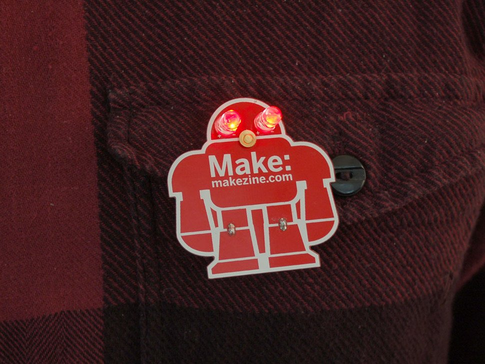 fully assembled red robot badge showing lit up red LED eyes and the words MAKE: makezine.com on the front