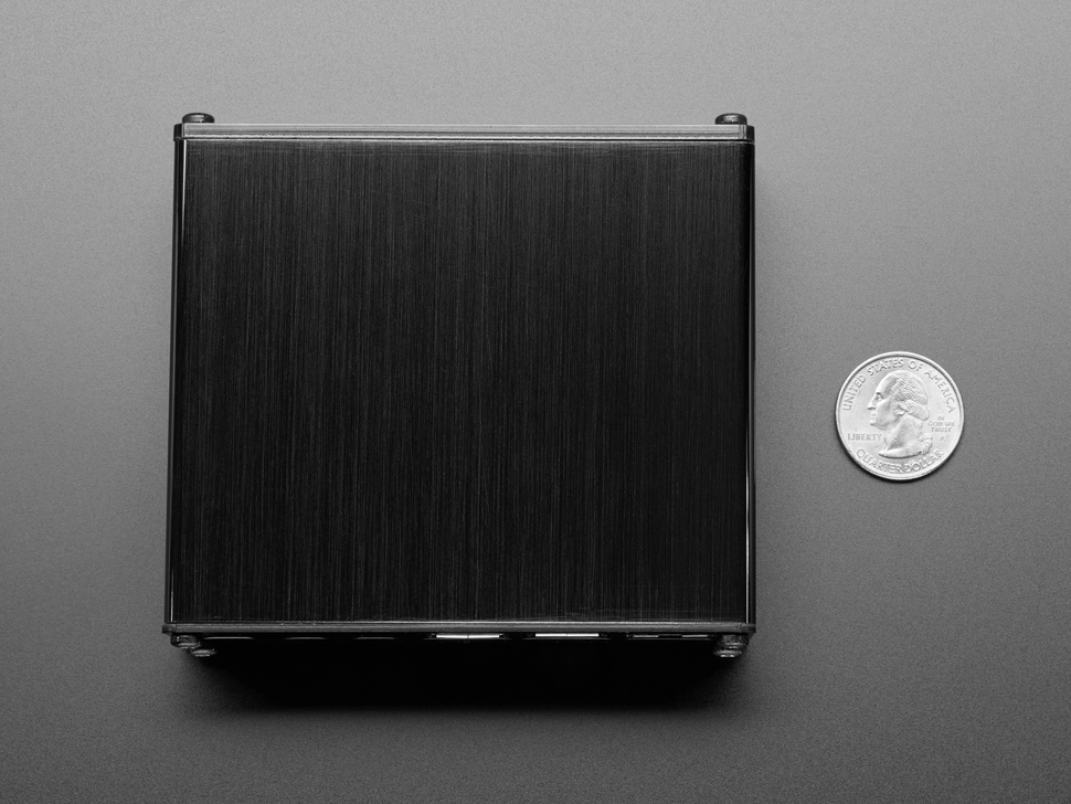 Bottom of assembled black aluminum Raspberry Pi enclosure next to US quarter.