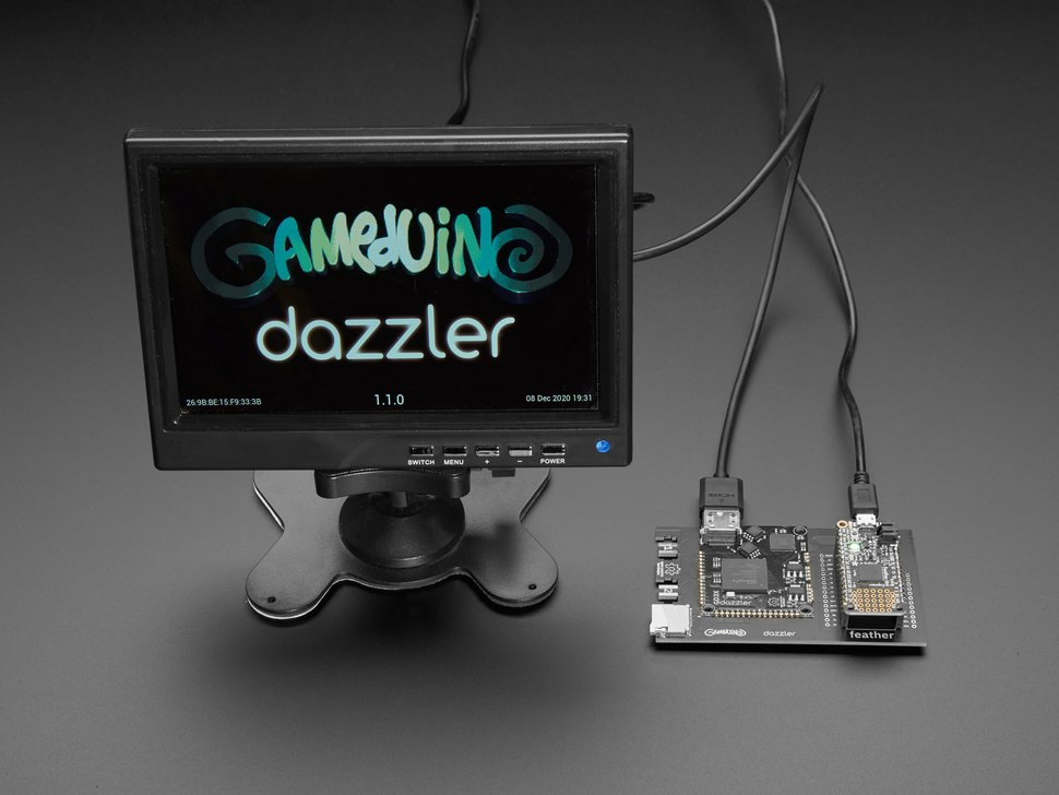Gameduino Dazzler PCB assembled with an Adafruit Feather M4 Express hooked up to a small monitor screen. The monitor displays the Gameduino Dazzler logo.