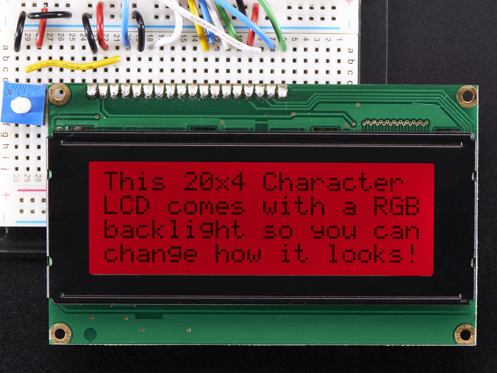 "LCD wired on breadboard with text displayed: ""This 20x4 Character LCD comes with an RGB backlight so you can change how it looks"" with red backlight"