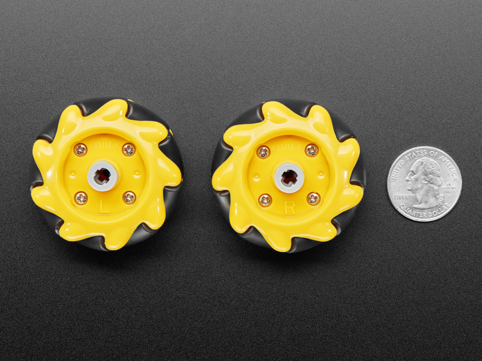 Bottom of left and right mecanum wheels next to US quarter for scale.
