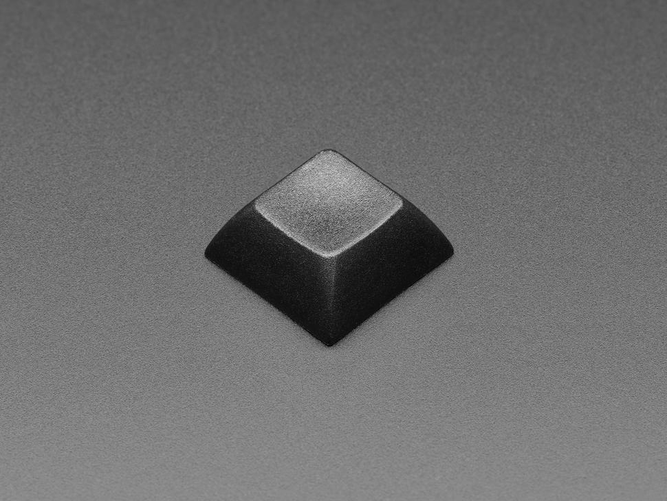 Angled shot of single black keycap.