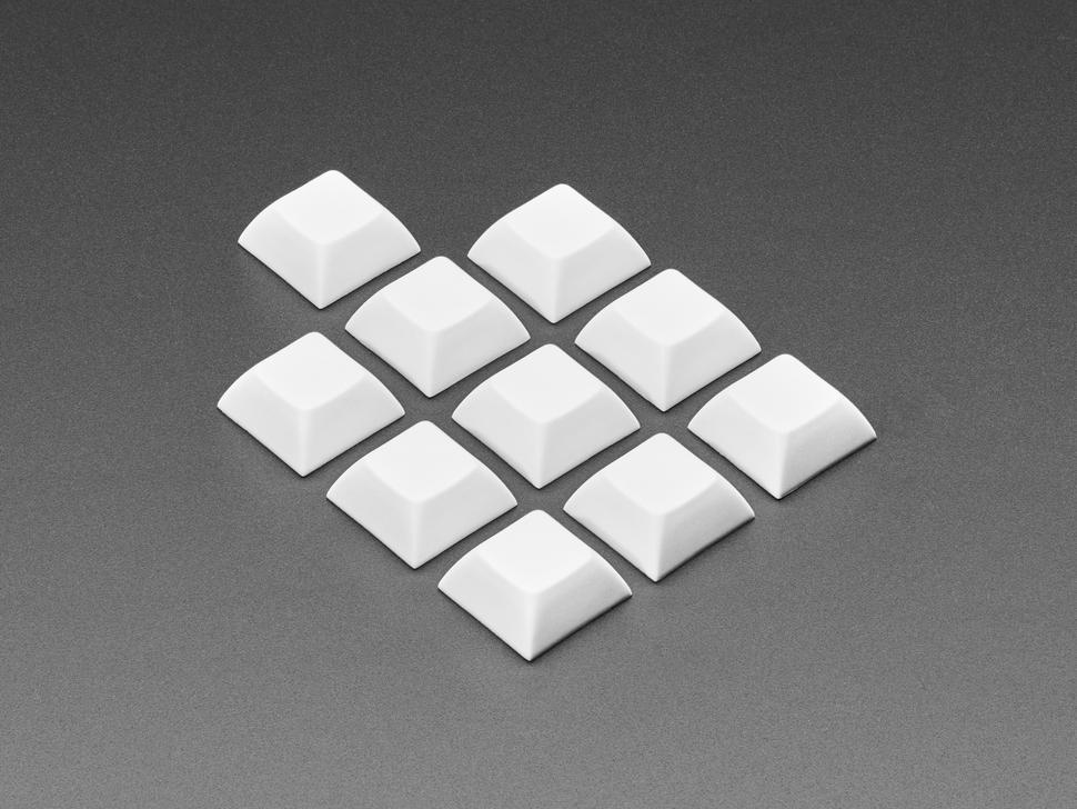 Angled shot of 10 white plastic keycaps.