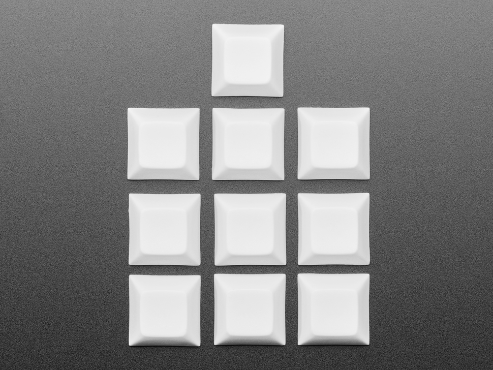 Top view of 10 white plastic keycaps.